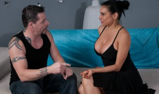 Sheila Marie wearing a tiny black dress that shows massive cleavage