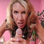 sexy mature woman stroking a client's cock